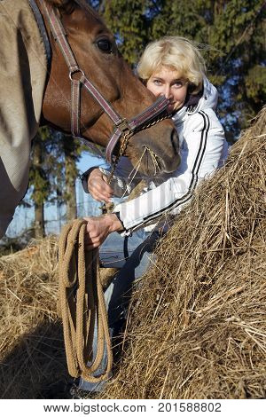 LATVIA, RIGA, OCTOBER, 20, 2015 - Portrait of cute young woman hugs his horse, who eats hay from a stack outside the stables in Riga, Latvia