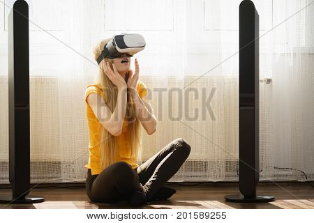 Young woman wearing virtual reality goggles vr 3d box sitting on floor in living room listening to music. Connection technology new generation and progress concept.