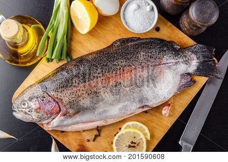 Trout spent raw on a cutting wooden board with spices, herbs, salt and olive oil