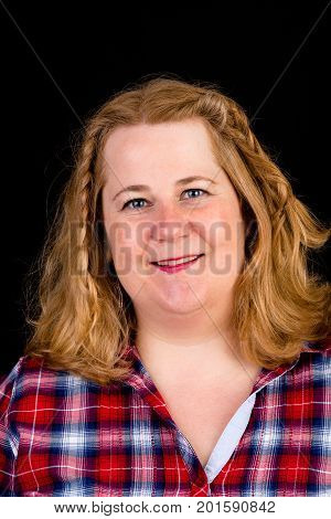 Portrait of a attractive european light overweighted red haired female with red lumberjack shirt - view on head, studio shot in fron of black background