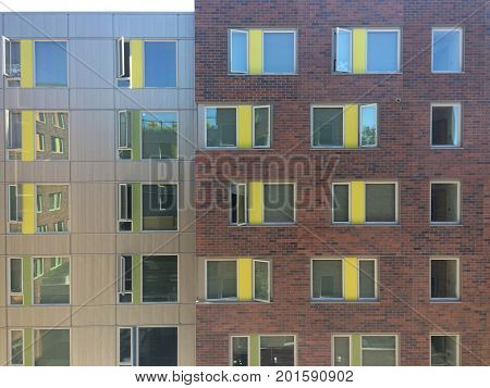 Dorm building with multiple reflections on windows, on clear day.
