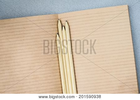 Pencils and open notebook paper from craft paper, top view, texture. Place for text, concept of starting school and any new cases