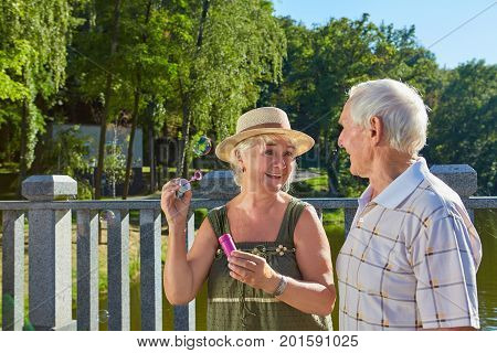 Old couple with bubble blower. Senior people, summer park background. Why having fun is important.