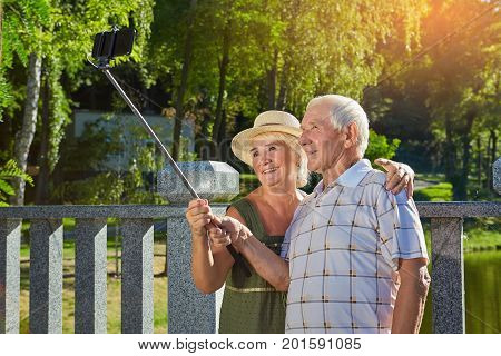 Happy old couple taking selfie. Smiling people outdoors. Vacation spots for retirees.