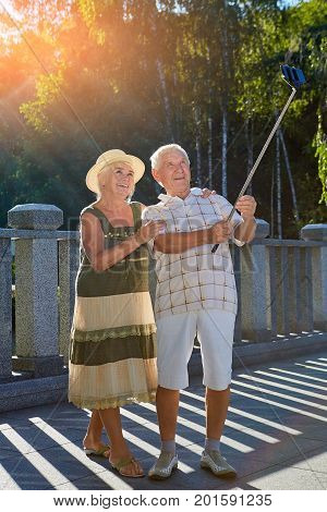 Senior couple taking selfie, summer. Old woman and man outdoors.