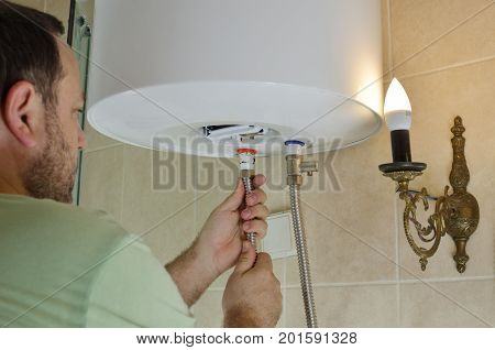 Man installing pipes for hot and cold water on a boiler in a bathroom