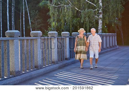 Elderly couple walking outdoors. Happy senior people holding hands. Retirement planning tips.