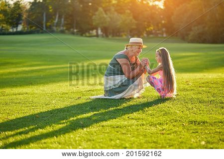 Happy grandma with granddaughter. People and green grass. Kids are the future.