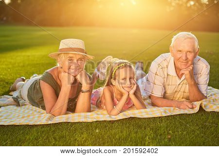Happy grandparents with grandchild. People lying outdoors summer.