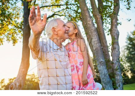 Girl whispering to her grandfather. Smiling senior man outdoors. The family secret.