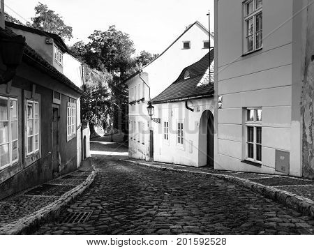 Old medieval narrow cobbled street and small ancient houses of Novy Svet, Hradcany district, Prague, Czech Republic. Black and white image