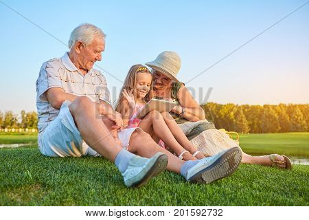 Smiling girl with grandparents, tablet. Happy people sitting on grass. How internet makes life easier.