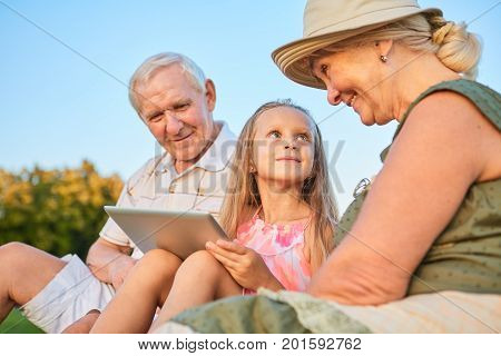 Child with a tablet, grandparents. Happy grandma looking at granddaughter.