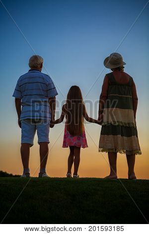 Girl with grandparents, sunset sky. Seniors and grandchild evening.