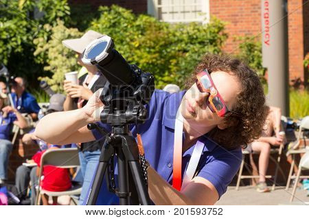 SALEM, WASHINGTON, USA - AUGUST 21, 2017: Eclipse enthusist adjusts camera with solar filter while wearing regular and eclipse safety glasses.