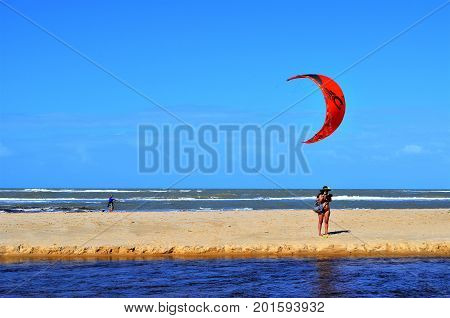 Beach of the Natives, Trancoso, Bahia, Brazil. July 29, 2017: Tourist photographing nature at the mouth of the River Trancoso. In the background, kitesurfing