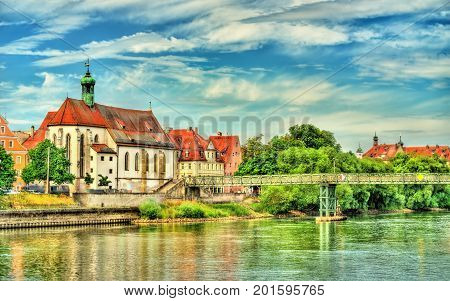 St. Oswald Church with Eiserner Steg bridge across the Danube River in Regensburg - Germany