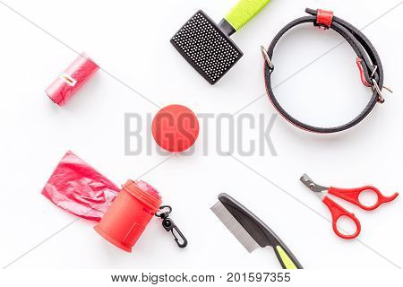 care about pet with collar and red grooming equipment on white table background top view