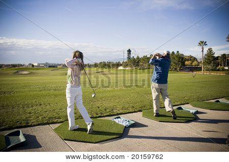 golf swings at the practice range