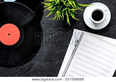 Desk of musician or dj with vynil records and blank paper for songwriter work set on dark background top view mockup
