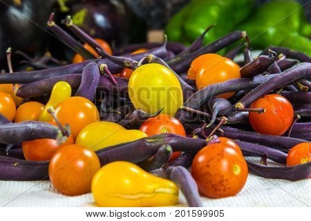 Horizontal photo of colorful tomatoes purple beans bell peppers and eggplant on a white surface