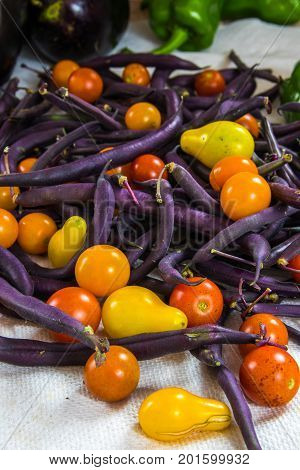 Vertical photo of colorful tomatoes purple beans bell peppers and eggplant on a white surface