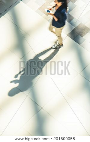 Silhouette of a walking woman with long shadow from above. Abstract background of blur in motion figure of a girl. Motion blur technique of low speed shot