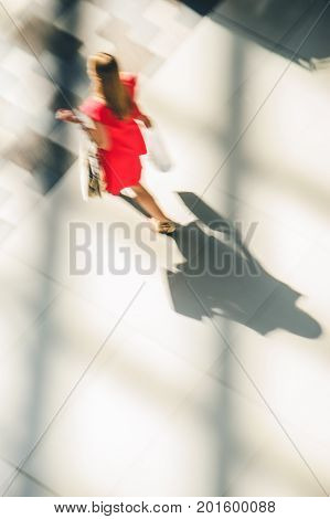 Silhouette of a walking woman with long shadow from above. Abstract background of blur in motion figure of a yang woman in red dress. Low speed shutter shot. Shopping concept