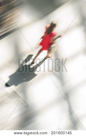 Silhouette of a walking woman with long shadow from above. Abstract background of blur in motion figure of a yang woman in red dress in a public building hall top view. Low speed shutter shot. Blurred Abstract Background.