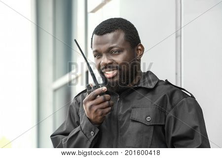 Male security guard using portable radio transmitter outdoors