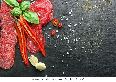Delicious sliced sausage, chili pepper, garlic and salt on grey background