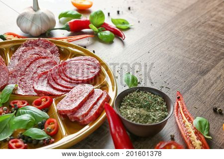 Plate with sliced different sausages and spice on table