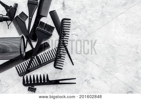 black combs, brushes for hairdresser work set on stone desk background top view mock up