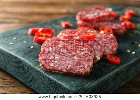 Wooden board with delicious sliced sausage and chili pepper on table