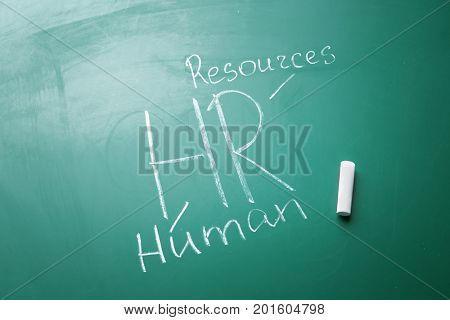 Management abbreviation HR with its full form written on chalk board