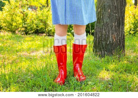 Young woman in red wellington boots outdoors