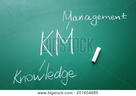 Management abbreviation KM with its full form written on chalk board