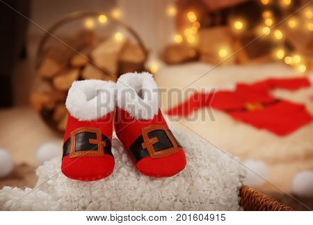 Christmas baby booties on fluffy fabric against blurred background