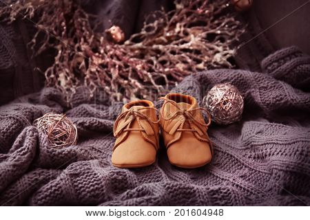 Baby booties on knitted fabric. Christmas concept
