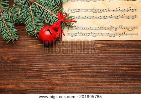 Beautiful composition with decorations and music sheet on wooden background. Christmas songs concept
