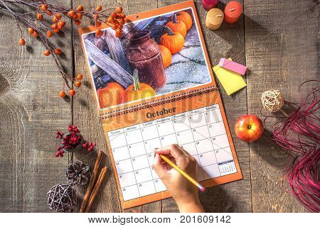 Open wall calendar with rustic October image female hand ready to write in square with pencil rustic wood plank table background with fall decor view from above