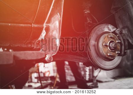 Car Lifted In Automobile Service For Fixing, Repair, Changing Brake Pads In Garage