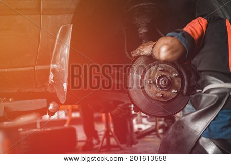 Professional Car Mechanic Changing Wheel In Auto Repair Service. Mechanic Men Adjusting The Tire At