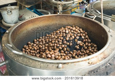 Roasting chestnuts on big pot from Gimyong market in Hatyai Thailand