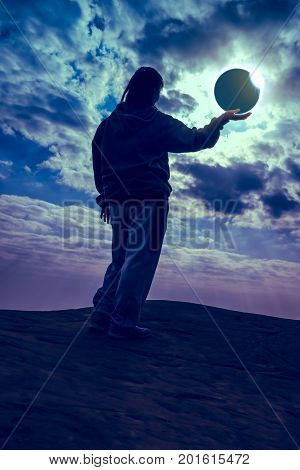 Amazing scientific natural phenomenon. Silhouette of woman enjoying total solar eclipse with diamond ring effect glowing on palm. Moon covering Sun. Golden sky with cloudy background surreal picture