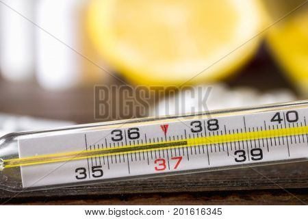 Glass Mercury Thermometer With A High Temperature Of 37.5 Against The Background Of Medicines, Lemon