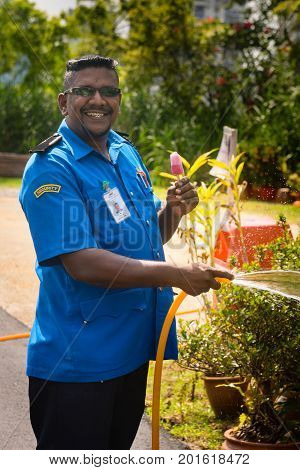 Smiling Security Guard Man With Ice-cream Waters A Lawn