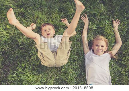 Two Happy Children Playing On The Grass At The Day Time.