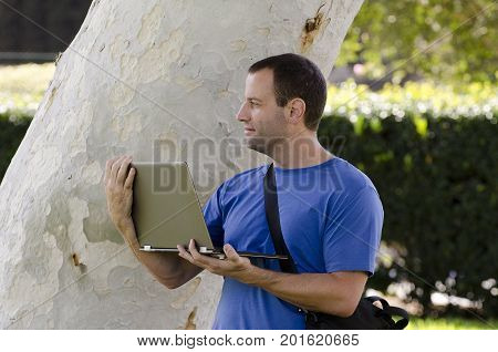 Man looking out while holding a lap top outside in front of a tree trunk.