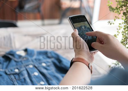 young start up small business owner holding mobile phone and take photo of her product. freelance woman entrepreneur SME use smart phone to take picture and sell cloth on website. Online selling internet marketing e-commerce concept